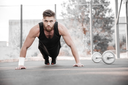 Portrait of a concentrated young bearded man athlete doing plank exercise outdoors
